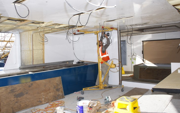 Installing custom made insulation panels to the deck head,bulkheads and ships sides of a trawlers fish processing area.