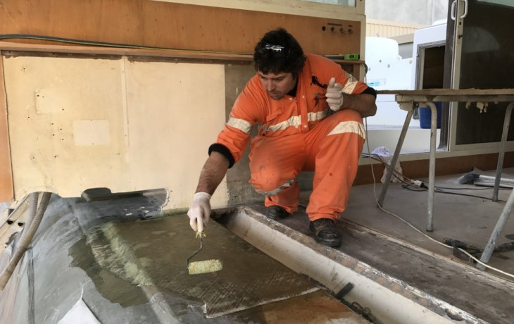 The long process of laminating and intergrating the side of the starboard hull and bridge deck underway.